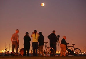 People watch as the blood moon rises over the water in Williamstown, Melbourne, Australia.