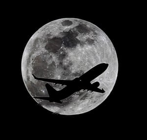 A plane crosses the moon's path over Whittier, California, approximately one hour before the total lunar eclipse.