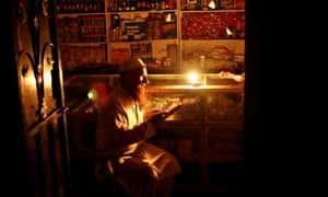 A store owner reads by candlelight