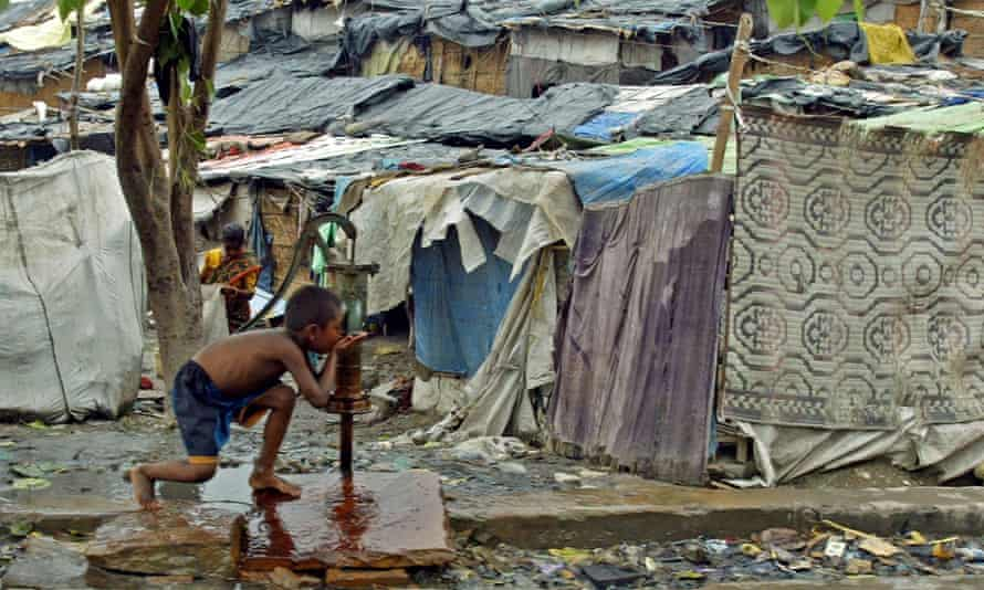 A boy drinks water from a pump near a slum on the banks of the Yamuna river in Delhi.