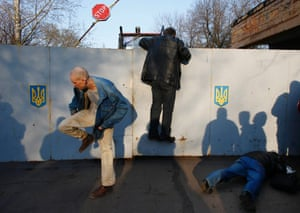A pro-Russia protester tries to climb over the fence of an Ukrainian airbase, next to fellow demonstrators in Kramatorsk, in eastern Ukraine April 15, 2014.