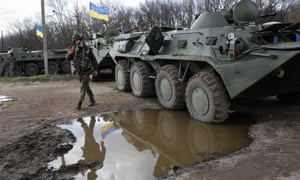 A Ukrainian soldier walks next to armed military vehicles, near the Izyum city in Kharkiv area, Ukraine, 15 April 2014.