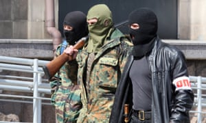 Armed pro-Russia activists walk outside the city state building they seized in the eastern Ukrainian city of Donetsk,
