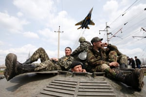 A fighter jet flies above as Ukrainian soldiers sit on an armoured personnel carrier in Kramatorsk, in eastern Ukraine April 16, 2014.