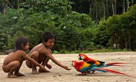 Huaorani Indian children play with scarlet macaws in Yasuni National Park