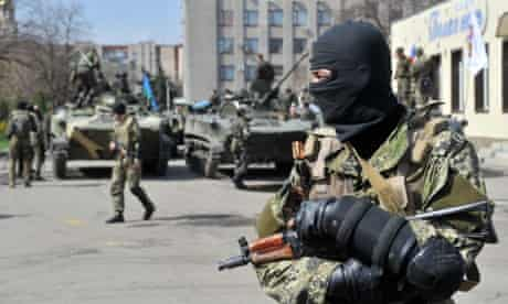 Armed men wearing military fatigues gather by APCs as they stand guard in Slavyansk, Ukraine.