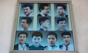 Photos showing example hair styles hang inside a barber shop in Pyongyang in 2013.