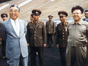 The late North Korean leaders Kim Jong-il (R) and then-leader, Jong-il's father, Kim Il-sung (L) inspect a football ground in Pyongyang