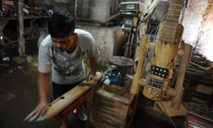 An artist works to make a bamboo lute and guitar in his workshop at Tanjung Wangi Village, Indonesia.