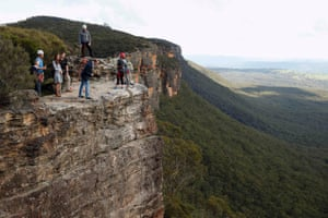 Prince William, leans over the cliff as Catherine, Duchess of Cambridge looks on while visiting the Narrow Neck Lookout and observe abseiling by the Mountain Youth Services group in the Blue Mountains in Katoomba, Australia.