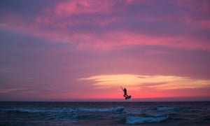 A man surfs with his kite in the Mediterranean sea in Ashkelon, Israel.