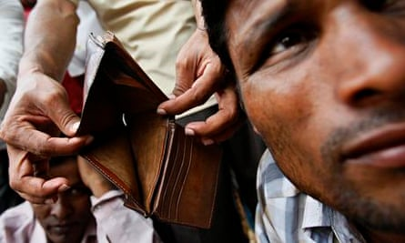 A migrant worker from Bangladesh shows his empty wallet to the camera in Singapore
