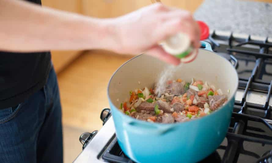 Man seasoning a pot of vegetables and meat