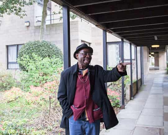 Sociable walkway … Resident Valentine Walker, 63, stands in the covered colonnade that runs through the site.