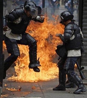 A member of the National Police runs away from fire after anti-government protesters threw a Molotov cocktail at them during clashes in Caracas. Anti-government protests have beset Venezuela since February, leaving at least 41 people dead and more than 600 injured.