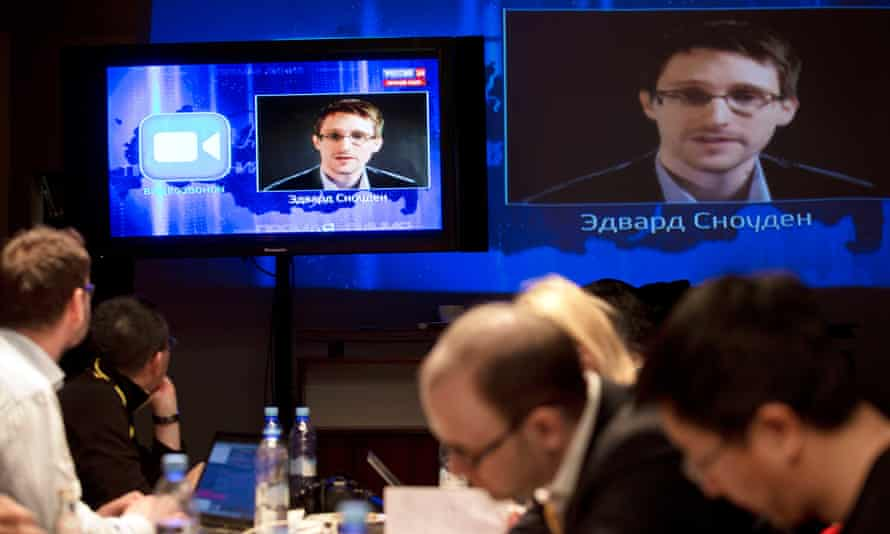Edward Snowden appears on television screens as he questions Vladimir Putin.