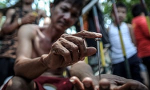 Danillo Castro shows a five-inch nail that will be used in his re-enactment of the crucifixion on Good Friday in San Fernando, Philippines