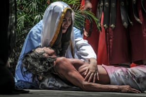 Penitents take part in a re-enactment of the  crucifixion in San Fernando, Philippines.