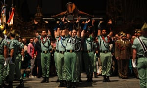 Spanish legionnaires carry a statue of the Christ  during a ceremony before they take part in the Mena brotherhood procession in Malaga, Spain.