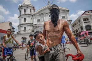 A hooded penitent carries his son outside the cathedral in San Fernando town, Philippines.