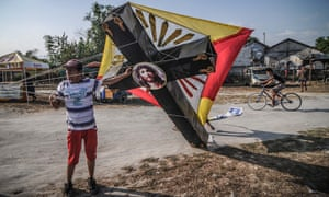 A Filipino prepares to fly a kite designed like a crucifix in Pampanga province, Philippines.