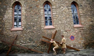 Performers carrying their cross before they take part in a re-enactment in Bensheim, Germany.