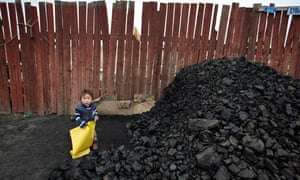 A child next to a heap of coal for sale by the roadside in Ulan Bator. Photograph: Dan Chung for the