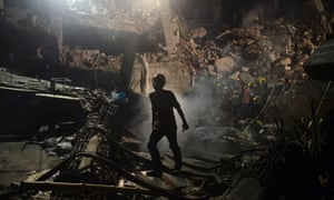 A Bangladeshi worker leaves the site where a garment factory building collapsed near Dhaka, Bangladesh.