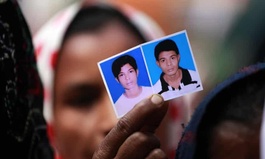 In Feb 2014, Dhaka, Bangladesh - A relative holds portraits of Rana Plaza victims during a human chain organised by National Garment Workers Federation demanding compensation for victims according to loss of earnings. The collapse of the Rana Plaza building in April last year killed 1,133 people and injured 2,500.