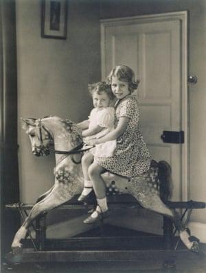Princess Elizabeth and Princess Margaret on a rocking horse, 1932.