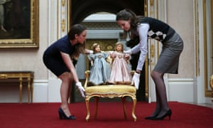 Royal Collection Trust Curators lift a chair containing Parisian dolls belonging to Queen Elizabeth II and Princess Margaret at Buckingham Palace.