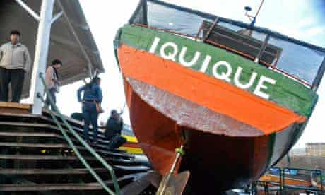 A boat washed onto a dock after a tsunami hit Iquique