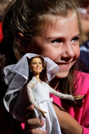 A girl holds a doll of  Catherine, Duchess of Cambridge as she waits outside St Andrew's Cathedral in Sydney, Australia