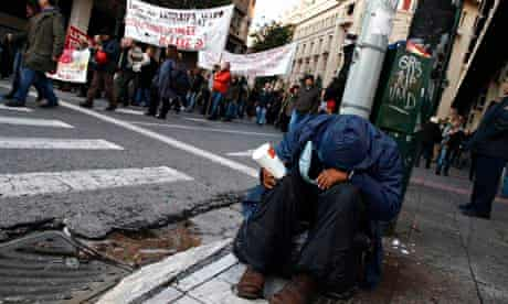 A man begs on a street in Athens during an anti-austerity demonstration