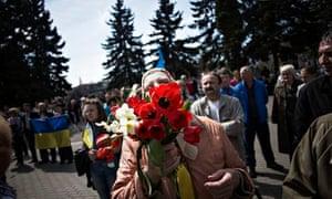 A Ukrainian woman holds a bouquet during a pro Ukrainian rally in Khartsyzk, Ukraine