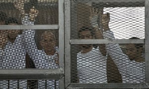 Australian journalist Peter Greste of Al-Jazeera and his colleagues stand inside the defendants cage during their trial.