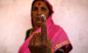 A woman shows her ink-marked finger