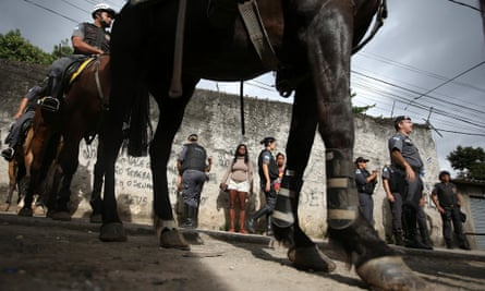 Military police on horseback patrol during a 'pacification' operation in the favela of Lins de Vasconcelos.