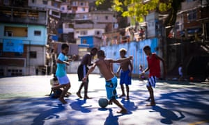 Boys play football in the Borel favela – previously controlled by drug traffickers but now occupied by the city's Police Pacification Unit