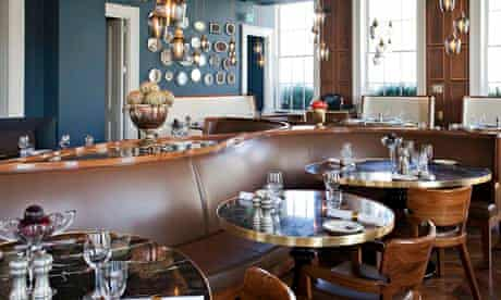 Curving banquette with round tables at Plum and Spilt Milk