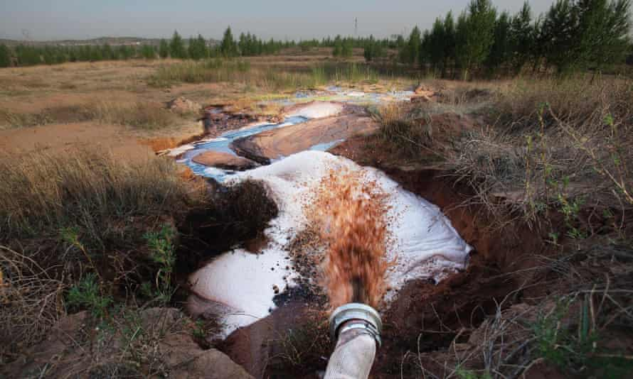 A pipe discharges factory waste water from the Shenhua coal-to-liquid project into a stream in the hills in Ordos in the Inner Mongolia Autonomous Region