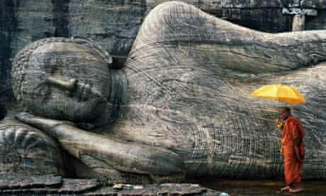A monk by a Buddha statue in Gal Vihara, Sri Lanka