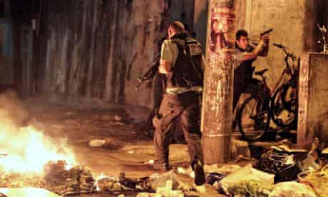 Military police on patrol near a burning barricade in Rio
