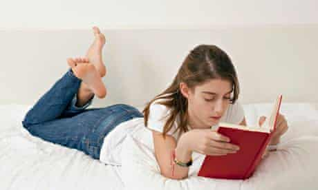 Girl lying on bed, reading book