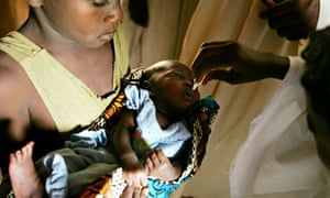 Nigerian field workers for the World Health Organisation inoculate a child with polio vaccine.