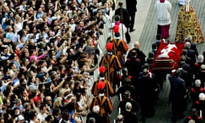 Pall bearers carry the body of Pope John Paul II through a crowded Saint Peter's Square.