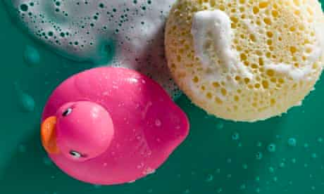 Rubber duck and sponge with soap foam, close-up