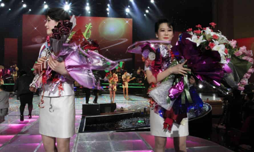 Singers of the Moranbong Band hold bouquets of flowers during their performance in Pyongyang, North Korea.