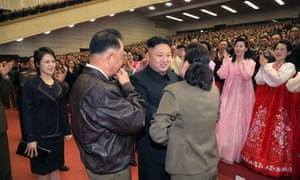 This photo released from North Korea's official Korean Central News Agency (KCNA) on April 20, 2014 shows Kim Jong-Un (C) speaking with the family of a military pilot at a performance given by the Moranbong Band