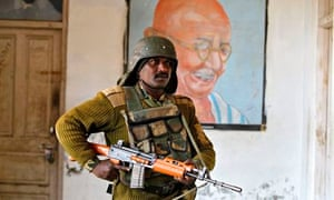 An Indian soldier stands guard at a polling station